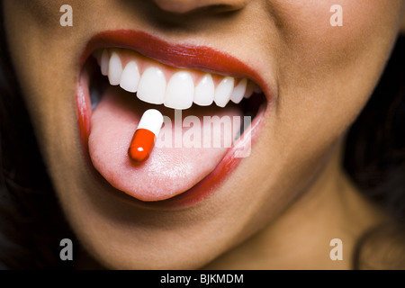Woman wearing red lipstick with a pill on tongue - Stock Photo