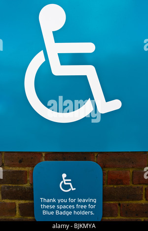 Sign advising motorists that these spaces are reserved for disabled persons with Blue Badges - Stock Photo