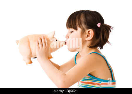Little girl with pigtails kissing a piggy bank - Stock Photo