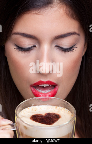 Woman drinking a cappuccino coffee with a love heart shape sprinking on top. - Stock Photo