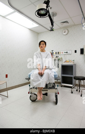 Female patient waiting anxiously in examining room - Stock Photo