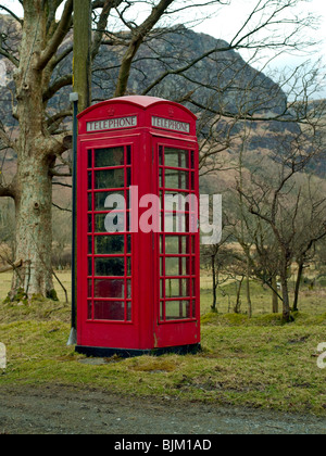 Old red British telephone box in a remote area, with mountain background and bare trees. - Stock Photo