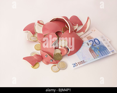 smashed broken pink piggy bank with euros & notes - Stock Photo