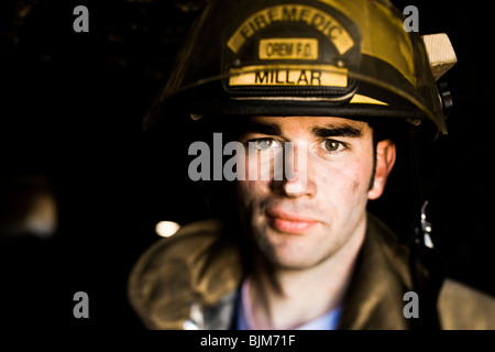 Portrait of a firefighter with fire hose - Stock Photo
