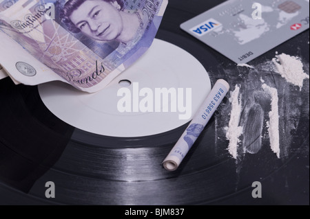 A picture showing cocaine use in the music industry with lines of white powder on a white label record and cash - Stock Photo
