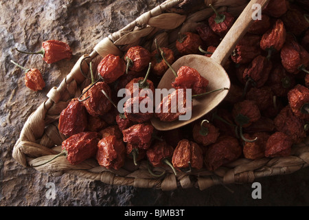 Mini-Peppers (Capsicum) with a wooden spoon in a wicker basket on a stone surface - Stock Photo