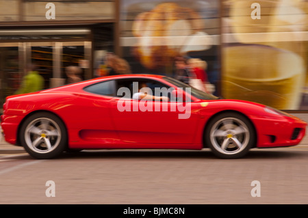 A red ferrari drives through the city showing movement with intentional blur in Norwich , Norfolk , England , Britain - Stock Photo