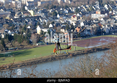 Workers in a safety cage navigate the suspension cable of a cable car which will connect the Deutsches Eck headland - Stock Photo