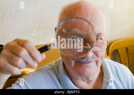 Pensioner looking through a magnifying glass - Stock Photo