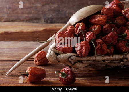 Mini-Peppers (capsicum) in a wicker basket on a rustic wooden background - Stock Photo