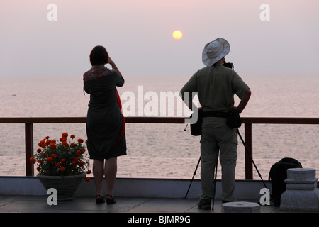 Woman taking a photograph and a photographer with a camera on a tripod in front of the sunset by the sea, Kovalam, - Stock Photo