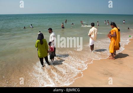 India, Kerala, Vypeen Island, Cherai Beach fully dressed Indian visitors bathing in the sea - Stock Photo