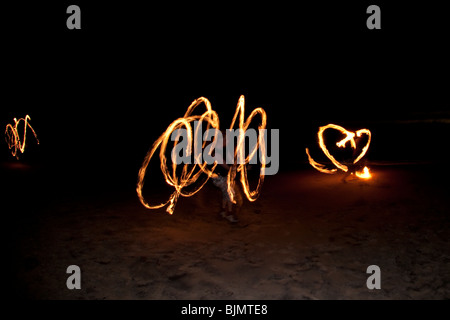 FIRE TWIRLING ON MOOLOOLABA BEACH - Stock Photo