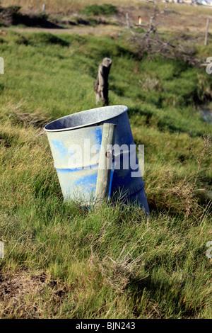 Rusty blue rubbish bin in green field. - Stock Photo