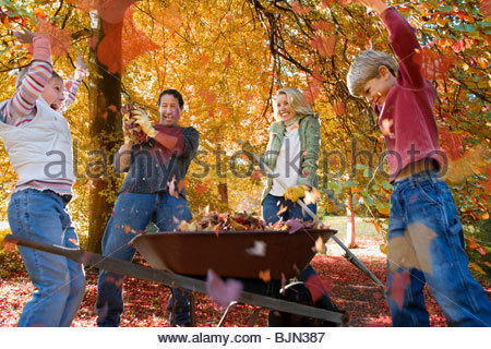 Family doing yard work and playing with autumn leaves - Stock Photo