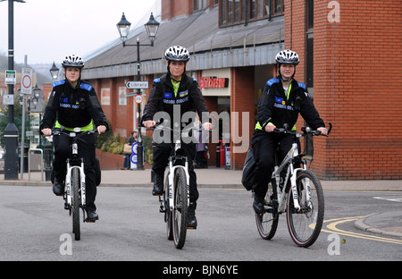 Three Police Community Support Officers patrolling on mountain bikes in Halesowen England Uk