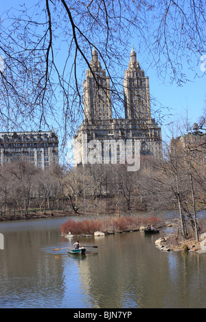 Rowboating on the lake in New York City's Central Park, with the San Remo apartment building on Central Park West - Stock Photo