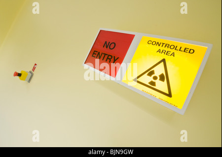 Radiation warning sign outside a radiotherapy unit in a West London hospital - Stock Photo