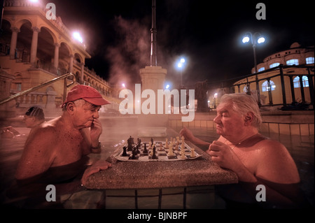 Men playing chess in the Szechenyi Baths on a cold winter night in Budapest, Hungary - Stock Photo