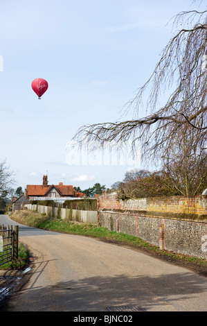 Virgin hot air balloon passing over a country road in the village of Hambleden in Buckinghamshire UK - Stock Photo