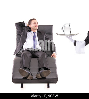 Young businessman relaxing on a sofa while the butler holding a pitcher - Stock Photo