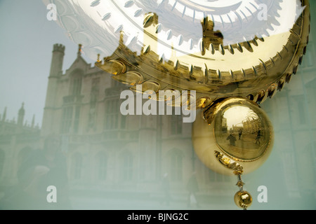 The pendulum of the Grasshopper Clock, Corpus Christi College cambridge, with Kings College reflected in the window, - Stock Photo