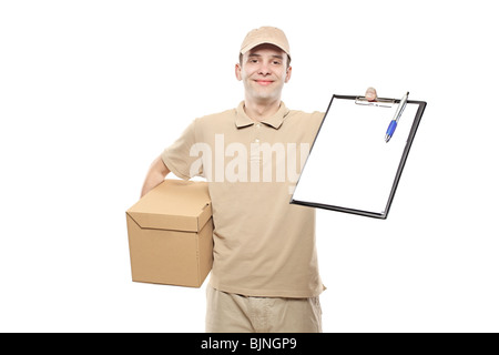 Delivery boy bringing a package and holding out a clipboard - Stock Photo