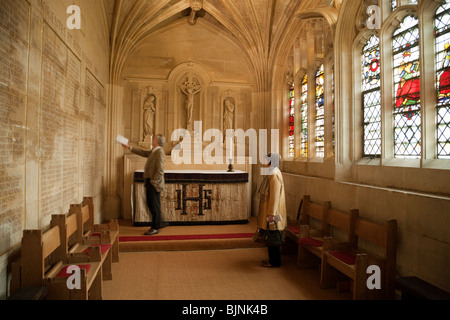Tourists looking at the names of the dead in World War 1, the Chapel, Kings College Chapel, Cambridge UK - Stock Photo