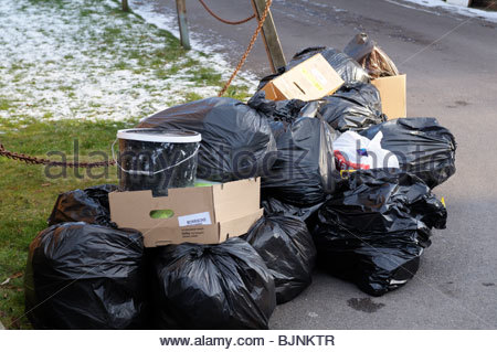 Close up of black rubbish bin bags left piled at the side of the road, England UK - Stock Photo
