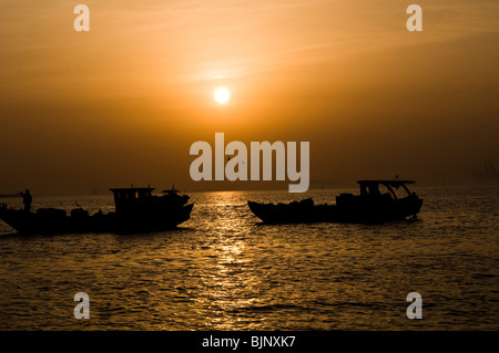 Fishing  boats during sunset in the south China sea. - Stock Photo