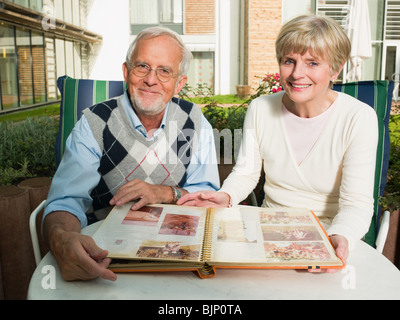 Senior couple looking at a photo album - Stock Photo