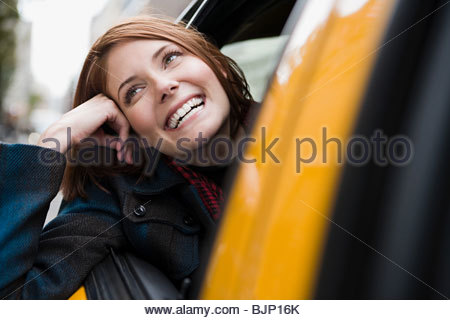 Young woman in a taxicab - Stock Photo