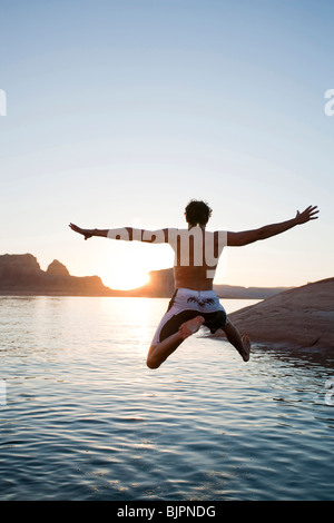 Man jumping into water at sunrise - Stock Photo