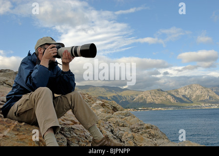 Man photographer taking a photograph of a landscape with telephoto lens, South Western Cape, South Africa - Stock Photo