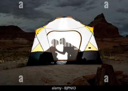 Silhouette of couple kissing in tent - Stock Photo
