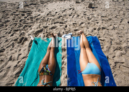 Legs of two women sunbathing at the beach - Stock Photo