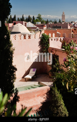 View on to a roof terrace in the Medina of Marrakesh with Atlas mountains in the distance - Stock Photo