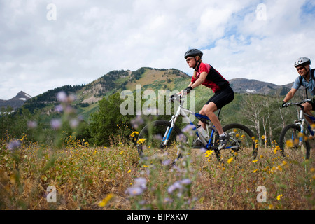 Woman biking on path outside - Stock Photo