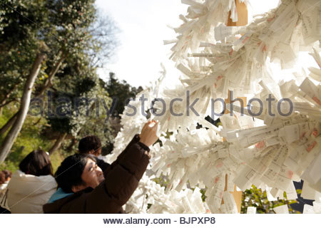 Omikuji prayers tied to string outside an Asian temple - Stock Photo