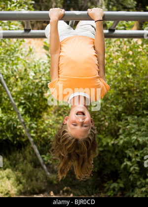 Upside down girl playing on bars - Stock Photo