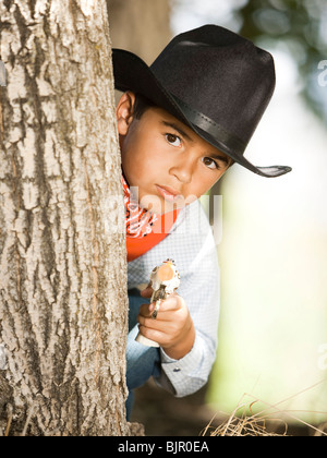 Boy in cowboy costume with toy gun - Stock Photo