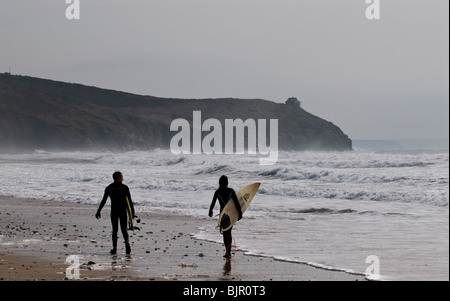 Two surfers walking along Praa Sands in Cornwall. - Stock Photo