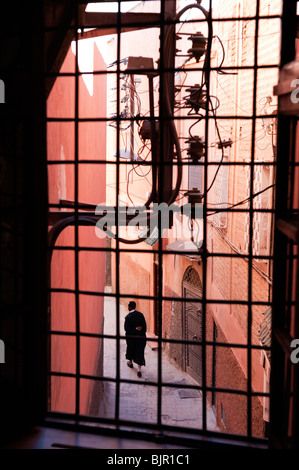A local man walking up a narrow lane in the medina of Marrakesh - Stock Photo