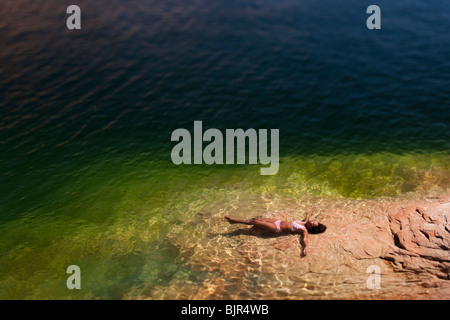 Woman lying in the water on back - Stock Photo