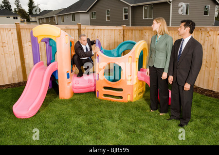 Three businesspeople playing on a jungle gym - Stock Photo
