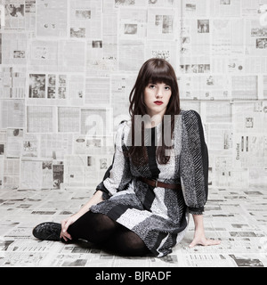 Young woman sitting on ground in room covered with newspapers, portrait, studio shot - Stock Photo