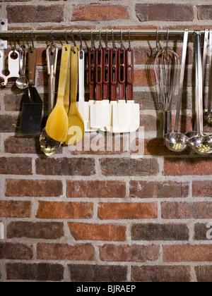 USA, Utah, Orem, close-up of cooking utensils hanging on rail - Stock Photo