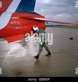 Red Arrows pilot Flt Lt. Si Stevens makes a pre-flight check of his Hawk jet aircraft before practice sortie above - Stock Photo
