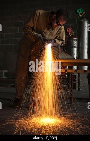 USA, Utah, Orem, man welding metal in workshop - Stock Photo