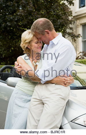 Senior couple leaning on car - Stock Photo